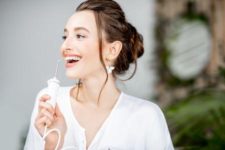 Ritratto di una bella donna con un sorriso brillante che tiene in mano uno strumento per l'irrigazione per la pulizia dei denti in bagno