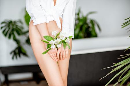 Mooi vrouwenlichaam met bloem die haar intieme plek in de badkamer bedekt
