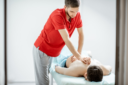 Young male therapist doing back massage to a man lying in the white cabinet of the rehabilitation clinic Imagens - 116442314