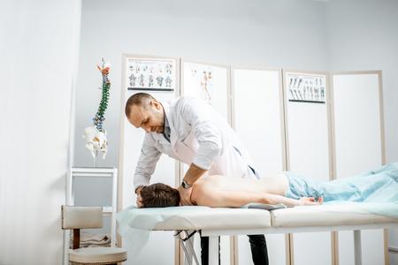 Fisioterapeuta senior profesional haciendo tratamiento manual a la columna cervical de un hombre en el gabinete de la clínica de rehabilitación