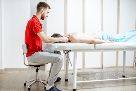 Young male therapist doing back massage to a man lying in the white cabinet of the rehabilitation clinic Imagens