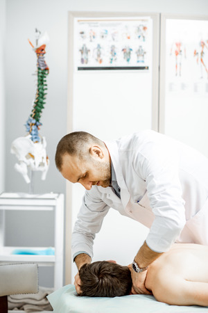 Professional senior physiotherapist doing manual treatment to a mans cervical spine in the cabinet of rehabilitation clinic