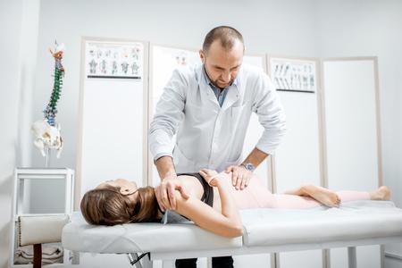 Fisioterapista professionista senior che fa un trattamento manuale a una giovane donna con problemi alla colonna vertebrale nel gabinetto della clinica di riabilitazione