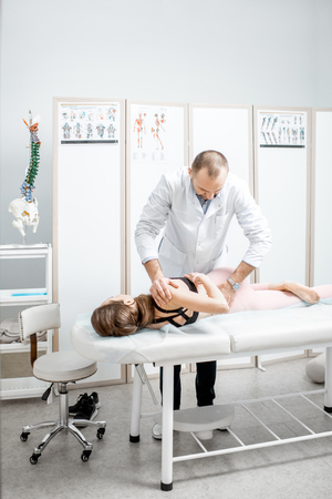 Professional senior physiotherapist doing manual treatment to a young woman with spine problems in the cabinet of rehabilitation clinic Zdjęcie Seryjne - 116442339