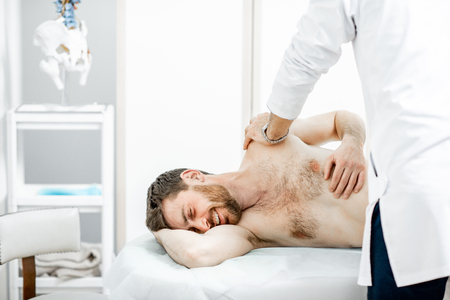 Professional senior physiotherapist doing manual treatment to a man in the cabinet of rehabilitation clinic Banque d'images