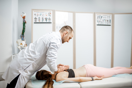 Professional senior physiotherapist doing manual treatment to a young woman with spine problems in the cabinet of rehabilitation clinic