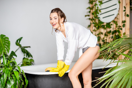 Attractive woman as a housewife in yellow protective gloves cleaning bathtub in the beautiful bathroom with green plants