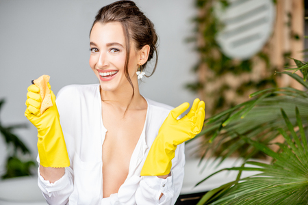 Portrait of a young and cheerful woman wearing yellow protective gloves as a housewife in the bathrrom Foto de archivo