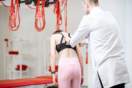 Physiotherapist looking on the woman's back during the medical examination at the rehabilitation office with suspension medical equipment