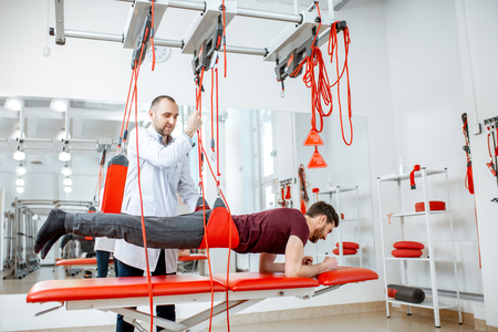 Senior physiotherapist doing treatment to a man with spine problems with suspension medical equipment at the rehabilitation clinic Standard-Bild