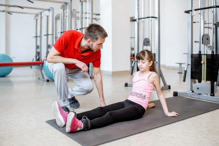 Trainer talking with young girl during the active treatment at the rehabilitation gym Standard-Bild