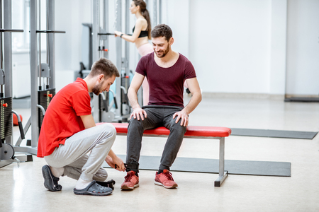 Trainer wearing cuffs on the patients legs preparing for the exercises at the rehabilitation gym Stock Photo