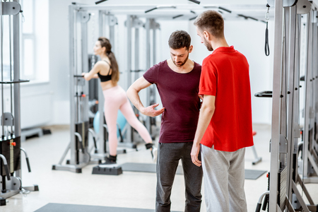 Therapist talking with man patient having problems with his back standing at the rehabilitation gym