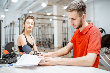 Man as a rehab in red uniform measuring pressure to a young woman sitting at the rehabilitation gym Stockfoto