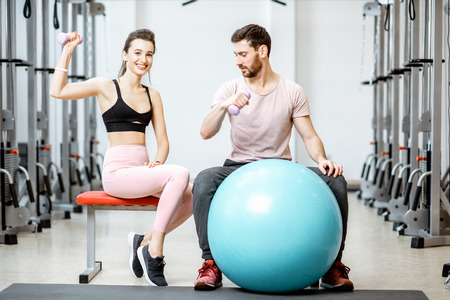 Portrait of a young sports couple sitting with fitness ball during the break at the rehabilitation gym Stock Photo