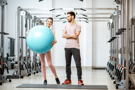 Sports trainer with young woman holding fitnesss ball standing together at the rehabilitation gym Stock Photo