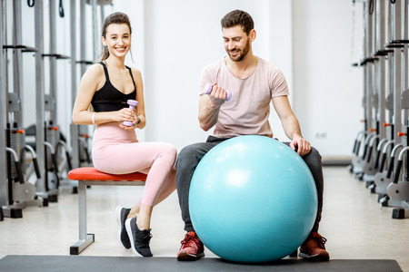 Portrait of a young sports couple sitting with fitness ball during the break at the rehabilitation gym Stock Photo - 116649444