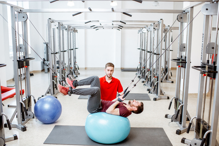 Man exercissing on the decompression simulators with trainer during the spine treatment at the rehabilitation gym