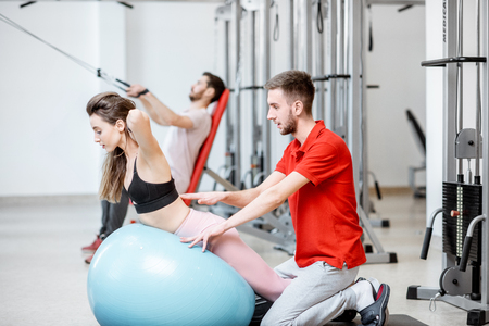 Young woman stretching on a fitness ball with man trainer during the spine treatment at the rehabilitation gym