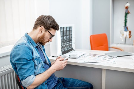 Man using smartphone sitting hunched down having scoliosis in the office of therapist at the clinic Stock Photo