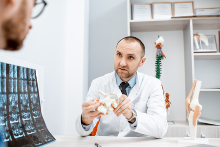Portrait of a senior therapist during the medical consultation showing anatomical model of vertebras in the office