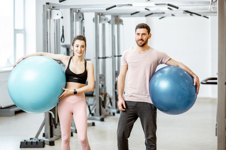 Portrait of a young sports couple standing with fitness balls at the rehabilitation gym Stock Photo