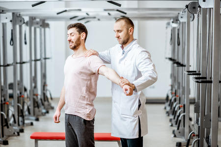 Professional senior physiotherapist doing manual treatment to a man standing in the rehabilitation gym Stockfoto