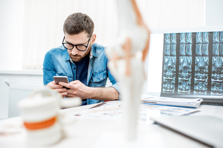 Man using smartphone sitting hunched down having scoliosis in the office of therapist at the clinic Stok Fotoğraf