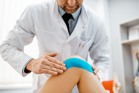 Therapist applying kinesio tape on a womans knee in the medical office. Medical treatment with kinesio tape 版權商用圖片 - 116650065