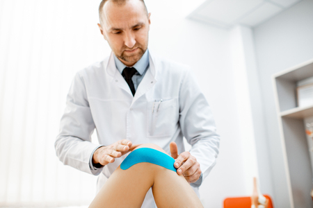 Therapist applying kinesio tape on a womans knee in the medical office. Medical treatment with kinesio tape