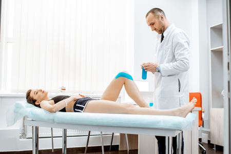 Senior therapist applying kinesio tape on a womans knee in the medical office. Medical treatment with kinesio tape Archivio Fotografico - 116650067