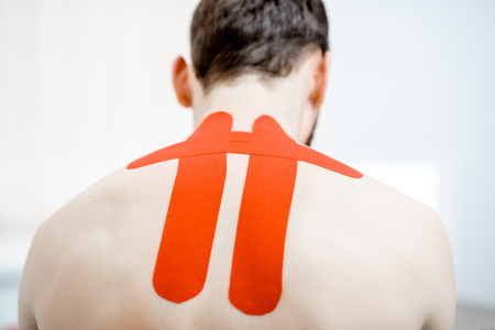 Mans neck with red kinesio tapes in the therapist office Stok Fotoğraf - 116650079