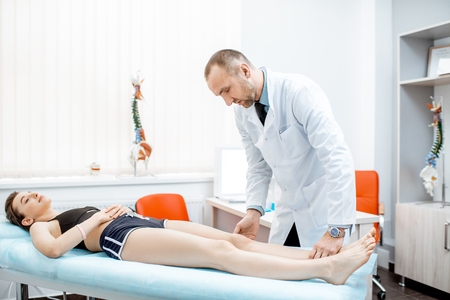 Woman lying on the medical couch during the examination with senior therapist in the office
