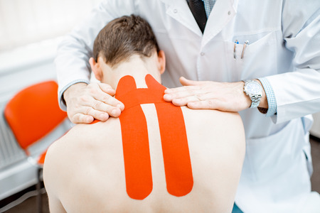 Senior therapist applying kinesio tape on a mans neck during the medical treatment in the office 版權商用圖片 - 116650103
