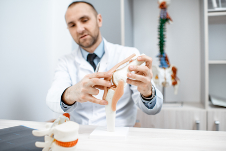 Senior therapist showing knee joint model during the medical consultation at the office