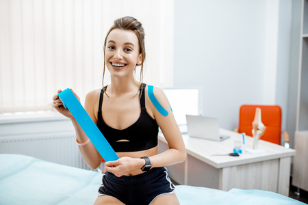 Portrait of a young and happy woman with kinesio tape during the medical treatment in the therapist office