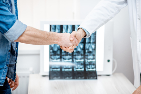 Handshake of the doctor and patient on the tomography print background at the therapist office