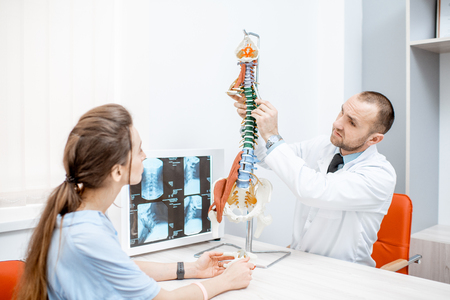 Young woman during the medical consultation with senior therapist showing spine model at the office