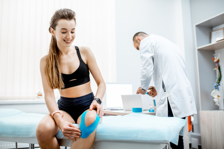 Young woman patient sitting with kinesio tape on her knee during the medical treatment with therapist in the office Archivio Fotografico - 116650167