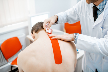 Senior therapist applying kinesio tape on a mans neck during the medical treatment in the office