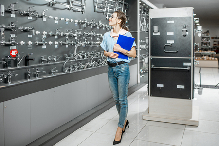 Young woman client choosing sanitary taps standing with catalog near the showcase of plumbing shop