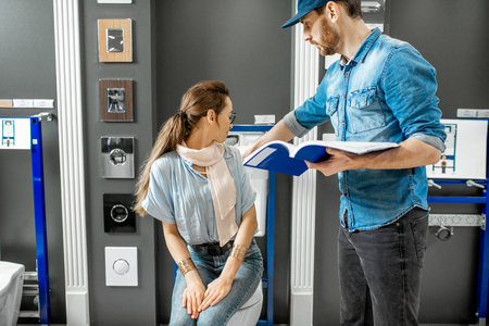Young woman with salesman or repairmman choosing a new ceramic bowl with drain system in the plumbing shop Standard-Bild - 116650265