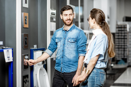 Young couple choosing buttons for drain of a new ceramic bowl in the plumbing shop Standard-Bild - 116650293