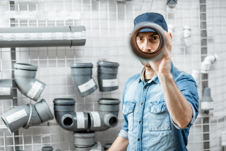 Funny portrait of a handsome workman choosing sewer pipes standing near the showcase of the plumbing shop