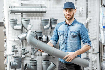 Portrait of a handsome workman choosing sewer pipes standing near the showcase of the plumbing shop