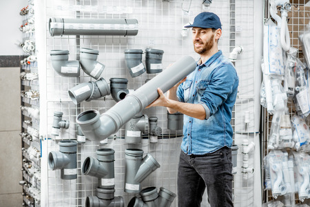 Handsome workman choosing sewer pipes standing near the showcase of the plumbing shop