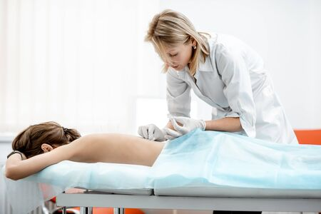 Neuropathologist puts needles into the womans back removing inflammation of the muscles during the acupuncture treatment in the office
