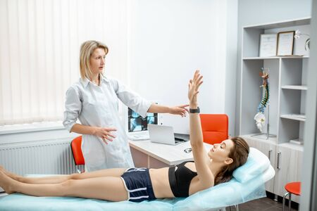 Young woman during the medical examination with neurologist testing reflexes in the office