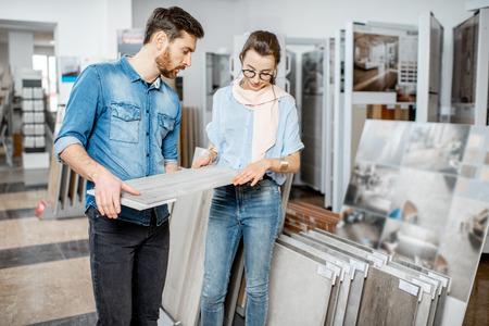 Schönes junges Paar, das Keramikfliesen für ihre Hausreparatur im Baugeschäft wählt Standard-Bild