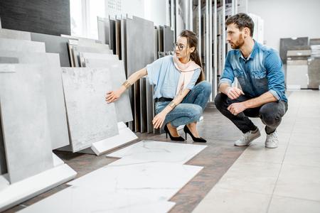 Hermosa joven pareja eligiendo grandes baldosas de granito para la reparación de su casa en el taller de construcción